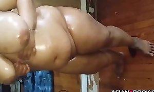 Obese asian babe inserts bottle